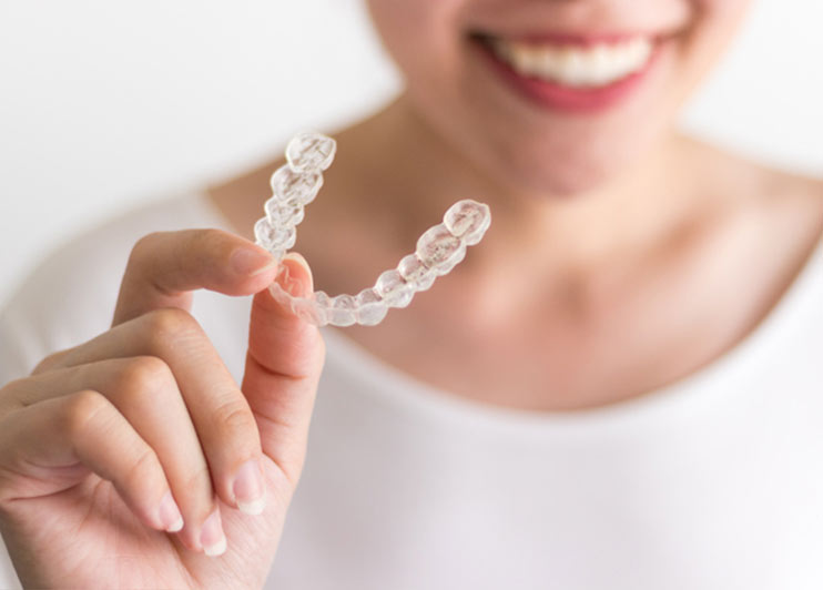 Smiling woman holding up a set of clear aligners