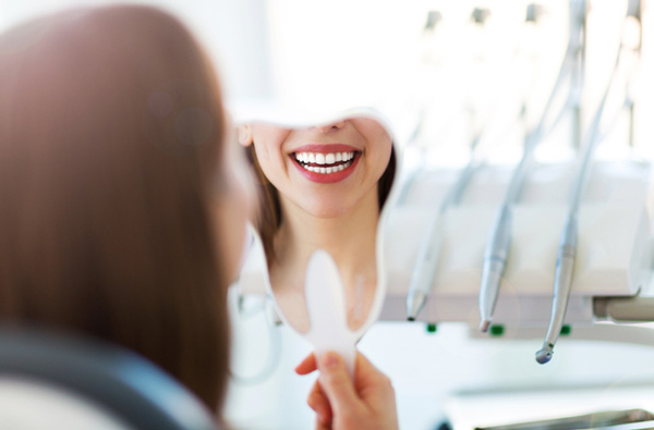 Woman looking at her new smile in a mirror